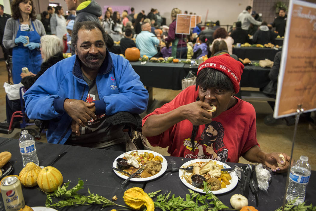 Husband and wife Dennis and Linda Norman enjoy their meal during Catholic Charities' annual Thanksgiving meal where about 175 volunteers help feed about 1,500 people from the Catholic Charities co ...