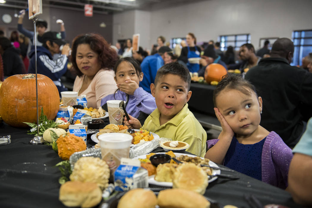 Mary Rocha, left, and her children Jazmine, 8, Caesar, 7, and Marissa, 3, enjoy family time during Catholic Charities' annual Thanksgiving meal where about 175 volunteers help feed about 1,500 peo ...