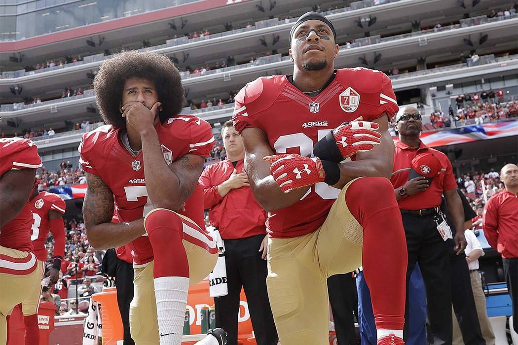 In this Oct. 2, 2016 file photo, San Francisco quarterback Colin Kaepernick, left, and safety Eric Reid kneel during the national anthem before a game against the Dallas Cowboys in Santa Clara, Ca ...