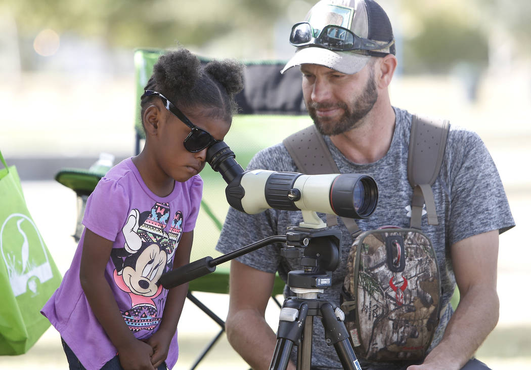 Nyriah, 3, who declined to give her last name, looks through spotting scope as Nathan Lemon, biologist with the Bureau of Reclamation, looks on during International Migratory Bird Day on Tuesday,  ...
