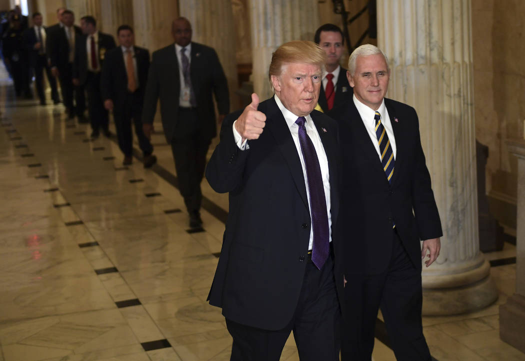 President Donald Trump gives a thumbs up as he walks with Vice President Mike Pence as he departs Capitol Hill in Washington, Thursday, Nov. 16, 2017. Trump urged House Republicans Thursday to app ...