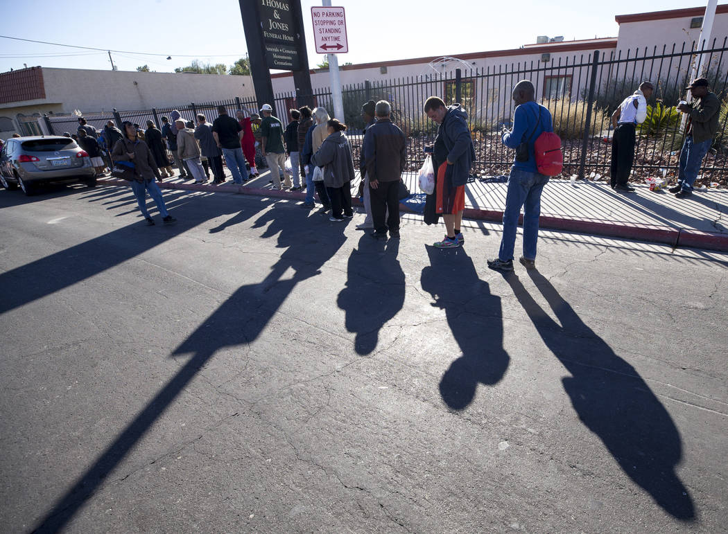 Homeless people wait for food handouts on Foremaster Lane between Las Vegas Boulevard and Main Street in Las Vegas, Wednesday, Nov. 22, 2017. Richard Brian Las Vegas Review-Journal @vegasphotograph