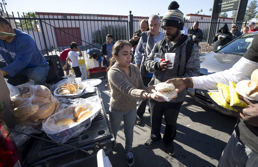 Homeless advocate Stephanie Bravo, center, hands out warm meals to a line of people on Foremaster Lane between Las Vegas Boulevard and Main Street in Las Vegas, Wednesday, Nov. 22, 2017. Richard B ...