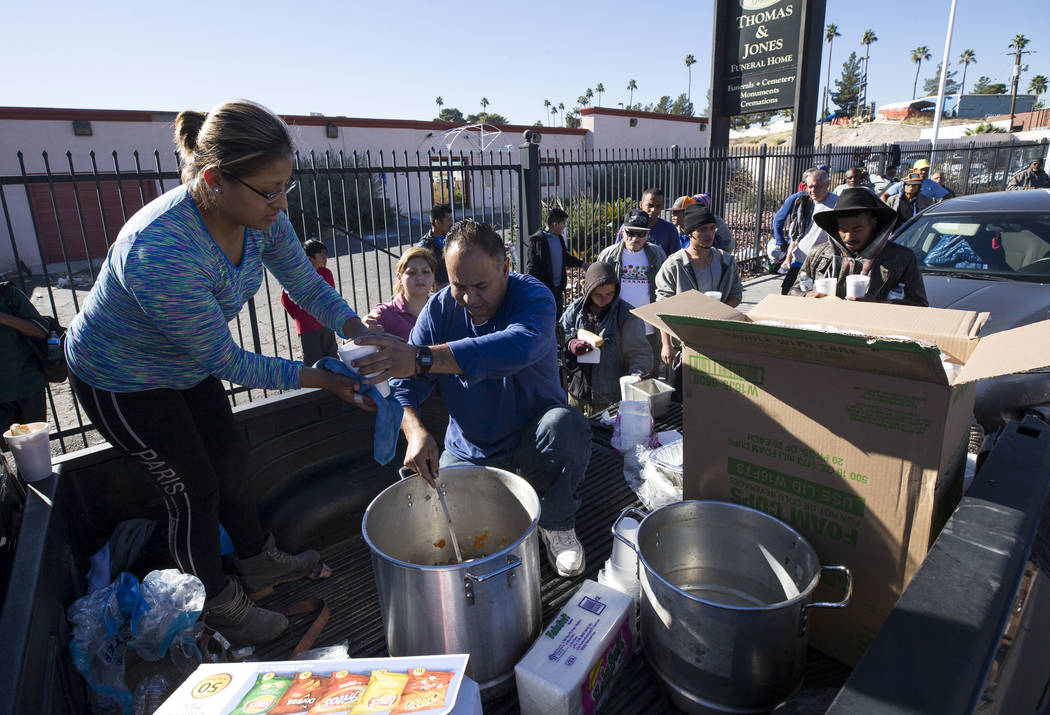 Homeless advocates Elizabeth Hernandez, left, and Matthew Romero hand out warm meals to a line of people on Foremaster Lane between Las Vegas Boulevard and Main Street in Las Vegas, Wednesday, Nov ...