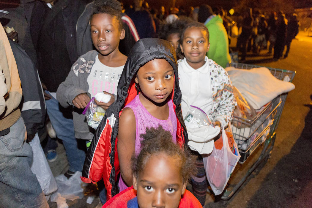 Siblings and cousins amongst other individuals wait in line to get winter coats and food with her siblings and cousins off of H Street and Bonanza Road in Las Vegas, Monday, Nov. 20, 2017.  Elizab ...