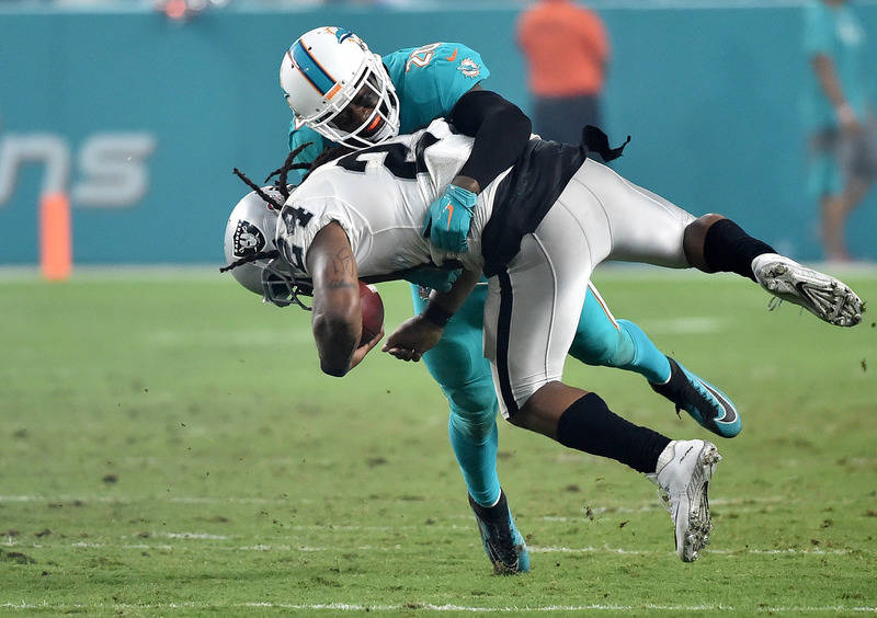 Nov 5, 2017; Miami Gardens, FL, USA; Miami Dolphins free safety Reshad Jones (20) tackles Oakland Raiders running back Marshawn Lynch (24) during the second half at Hard Rock Stadium. Mandatory Cr ...