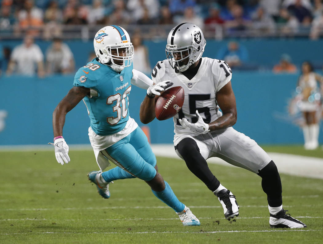 Oakland Raiders wide receiver Michael Crabtree (15) catches the ball ahead of Miami Dolphins cornerback Cordrea Tankersley (30), during the first half of an NFL football game, Sunday, Nov. 5, 2017 ...