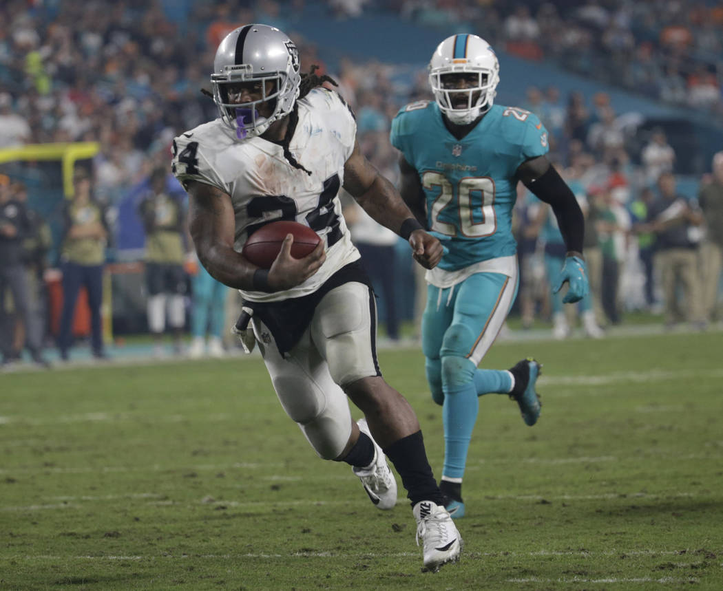 Oakland Raiders running back Marshawn Lynch (24) runs for a touchdown ahead of Miami Dolphins free safety Reshad Jones (20), during the second half of an NFL football game, Sunday, Nov. 5, 2017, i ...