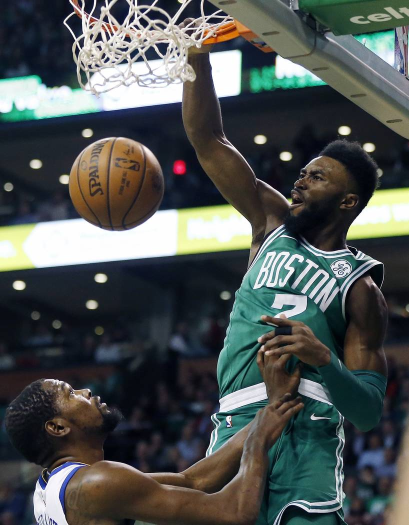 Boston Celtics' Jaylen Brown (7) dunks over Golden State Warriors' Kevin Durant during the first quarter of an NBA basketball game in Boston, Thursday, Nov. 16, 2017. (AP Photo/Michael Dwyer)