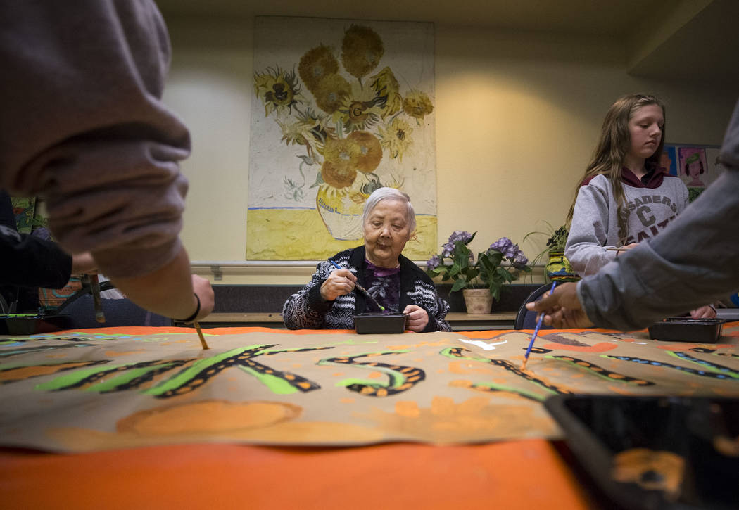Seventy-three-year-old Yuriko Ondo paints a Thanksgiving banner with a group of Faith Lutheran sixth graders volunteering at the Nevada Senior Services Adult Day Care Of Las Vegas on Friday, Nov.  ...