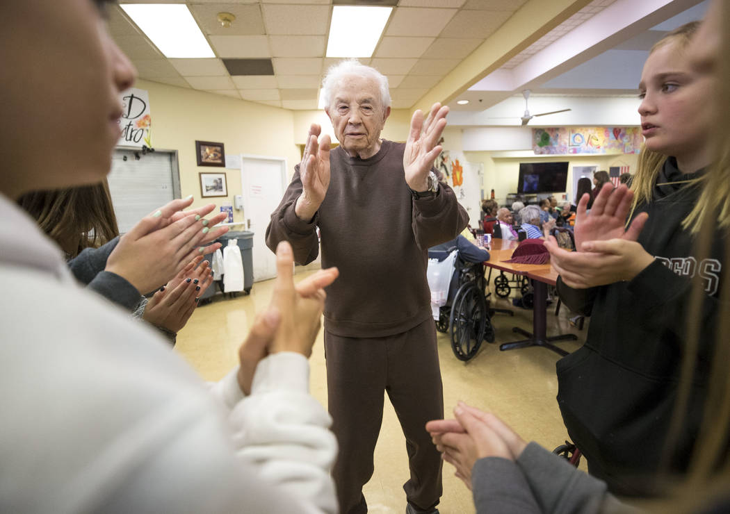 Ninety-year-old Leon Goldstein claps his hands during a dance with a group of Faith Lutheran sixth graders volunteering at the Nevada Senior Services Adult Day Care Of Las Vegas on Friday, Nov. 17 ...