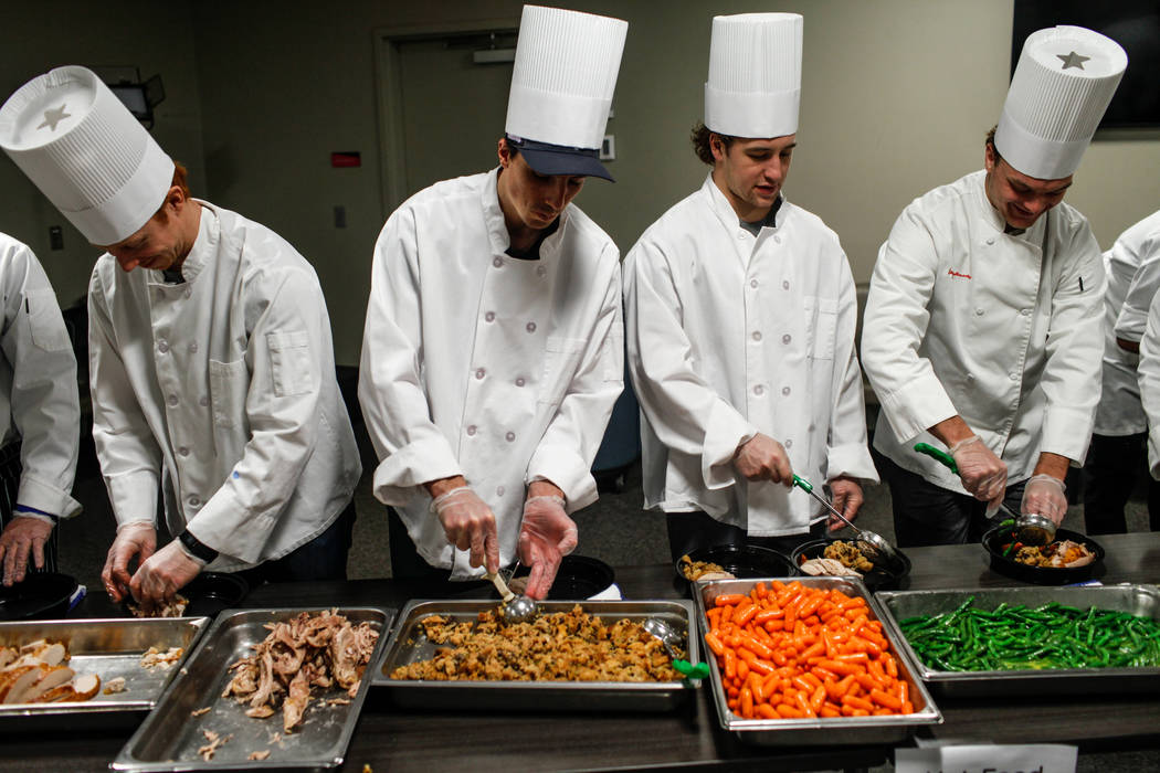 Vegas Golden Knights' Cody Eakin (21), left, Marc-Andre Fleury (29), second from left, Brendan Leipsic (13), second from right, and Reid Duke (37), right, prepare Thanksgiving meals for Three Squa ...
