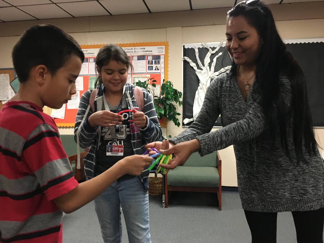 Yolanda Medrano hands bracelets to sixth-graders Angel Torres and Angela Gutierrez at the end of the day's after school program on Nov. 7. (Diego Mendoza-Moyers/View) @dmendozamoyers