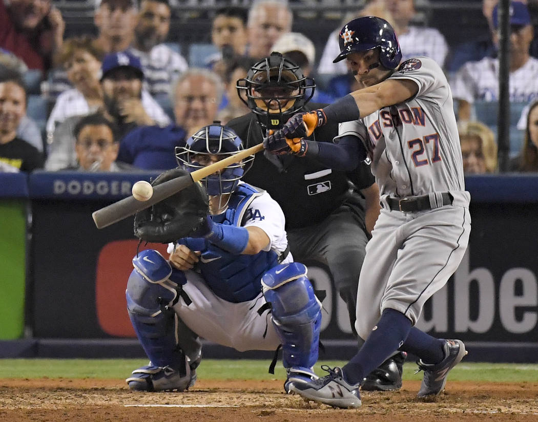 In this Oct. 25, 2017, file photo, Houston Astros' Jose Altuve hits a home run against the Los Angeles Dodgers during the 10th inning of Game 2 of baseball's World Series in Los Angeles. Houston d ...