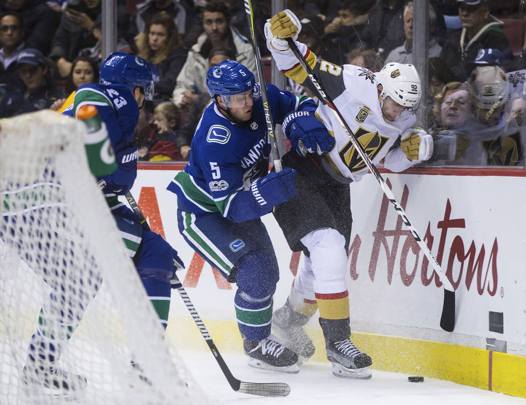 Vancouver Canucks' Derrick Pouliot (5) checks Vegas Golden Knights' Tomas Nosek (92), of the Czech Republic, during the first period of an NHL hockey game Thursday, Nov. 16, 2017, in Vancouver, Br ...