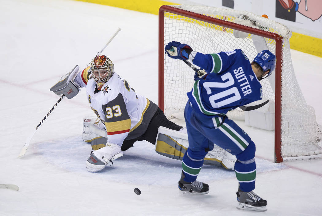 Vegas Golden Knights goalie Maxime Lagace, left, stops Vancouver Canucks' Brandon Sutter during the second period of an NHL hockey game Thursday, Nov. 16, 2017, in Vancouver, British Columbia. (Da ...