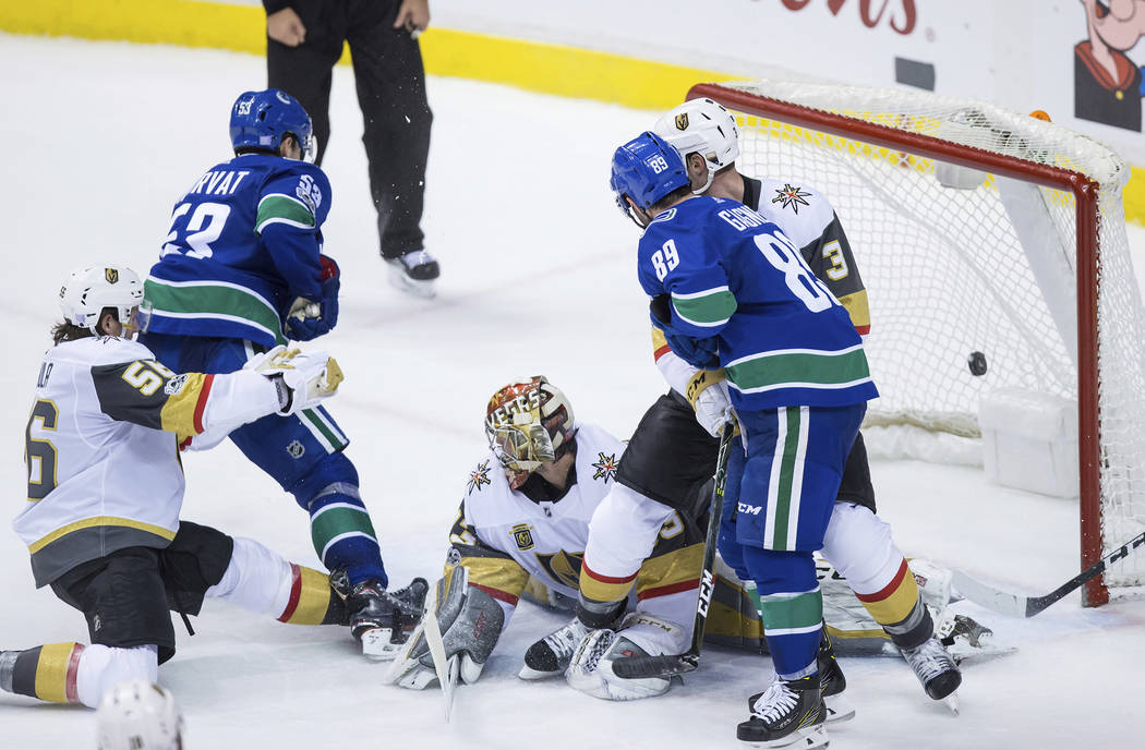 Vancouver Canucks' Bo Horvat (53) scores against Vegas Golden Knights goalie Maxime Lagace, center, while being checked by Erik Haula (56), of Finland, as Brayden McNabb (3) defends against Canuck ...