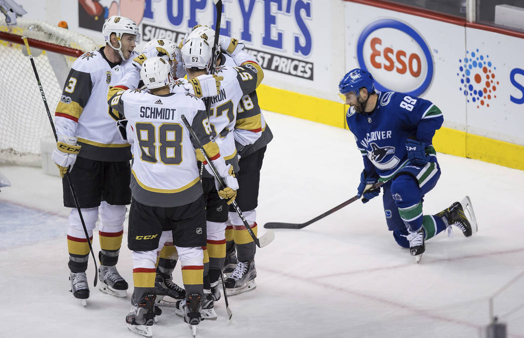 Vegas Golden Knights' Brayden McNabb; Nate Schmidt; Erik Haula, of Finland; David Perron; and James Neal, from left, celebrate Haula's goal as Vancouver Canucks' Sam Gagner pauses on the ice durin ...