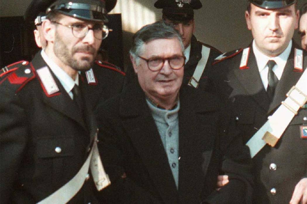 In this Jan. 16, 1996 file photo, Mafia ''boss of bosses'' Salvatore ''Toto'' Riina, center, enters handcuffed into Bologna's bunker-courtroom, escorted by Carabinieri, Italian paramilitary police ...