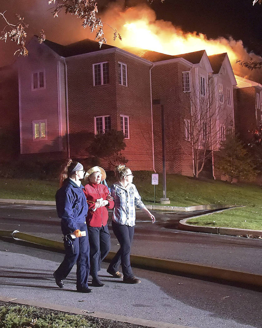 A resident of the Barclay Friends Senior Living Community is assisted away from the scene of a fire as the senior care facility burned late Thursday night, Nov. 16, 2017, in West Chester, Pa. The  ...