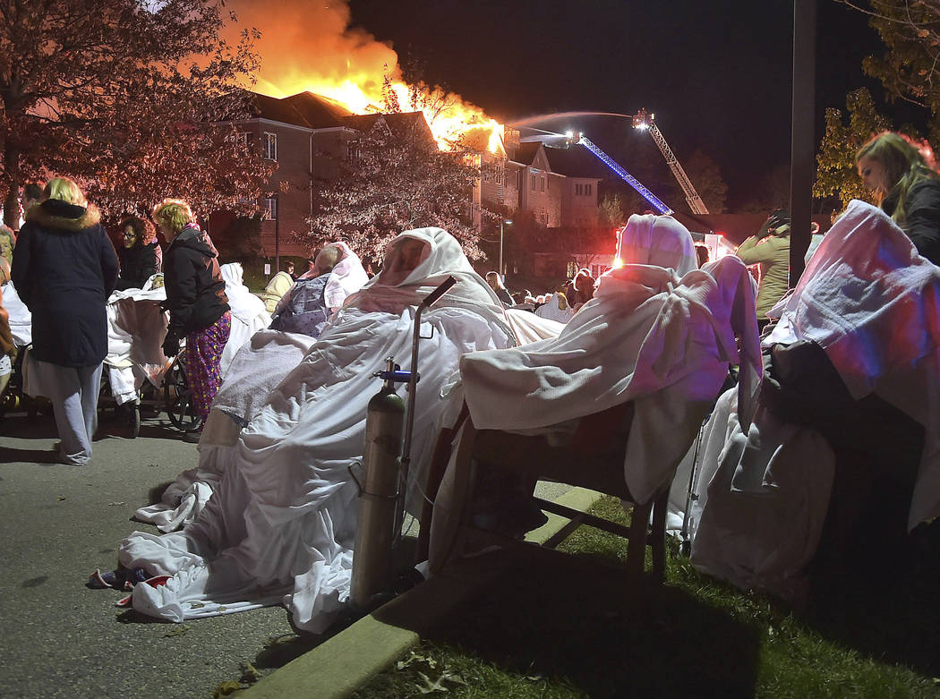 Residents of the Barclay Friends Senior Living Community wait to be taken to ambulances as the senior care facility burned in a massive fire, Thursday, Nov. 16, 2017, in West Chester, Pa. The fire ...