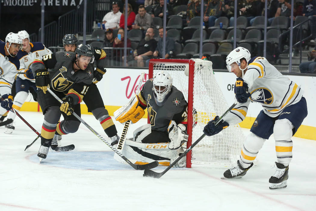 Vegas Golden Knights defenseman Jon Merrill (15) and Buffalo Sabres right wing Jason Pominville (29) fight for the puck in front of the Vegas Golden Knights goalie Malcolm Subban (30) during the s ...