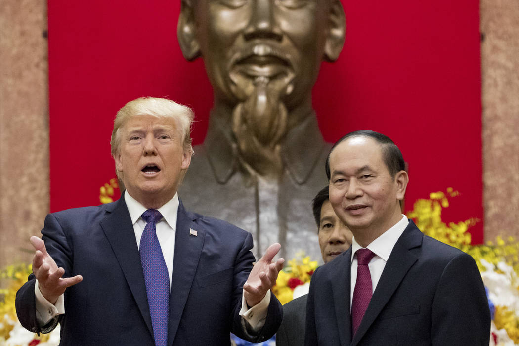 A large statue of Ho Chi Mihn is visible behind President Donald Trump and Vietnamese President Tran Dai Quang as they pose for photographers at the Presidential Palace, Sunday, Nov. 12, 2017, in  ...