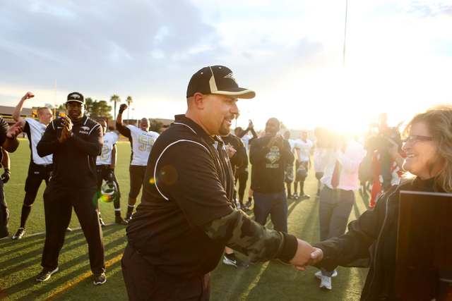 Spring Mountain's Head Coach Aaron Masden receives the trophy behalf of his team after they won the class 1A state football final neutral playoff game against Pahranagat Valley at Clark High Schoo ...