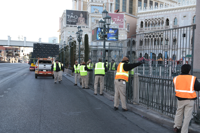 Workers disassemble the security barricade sections in front of the Venetian, as part of the final cleanup from the New Years' eve celebrations from the night before, the Venetian, Las Vegas, Satu ...