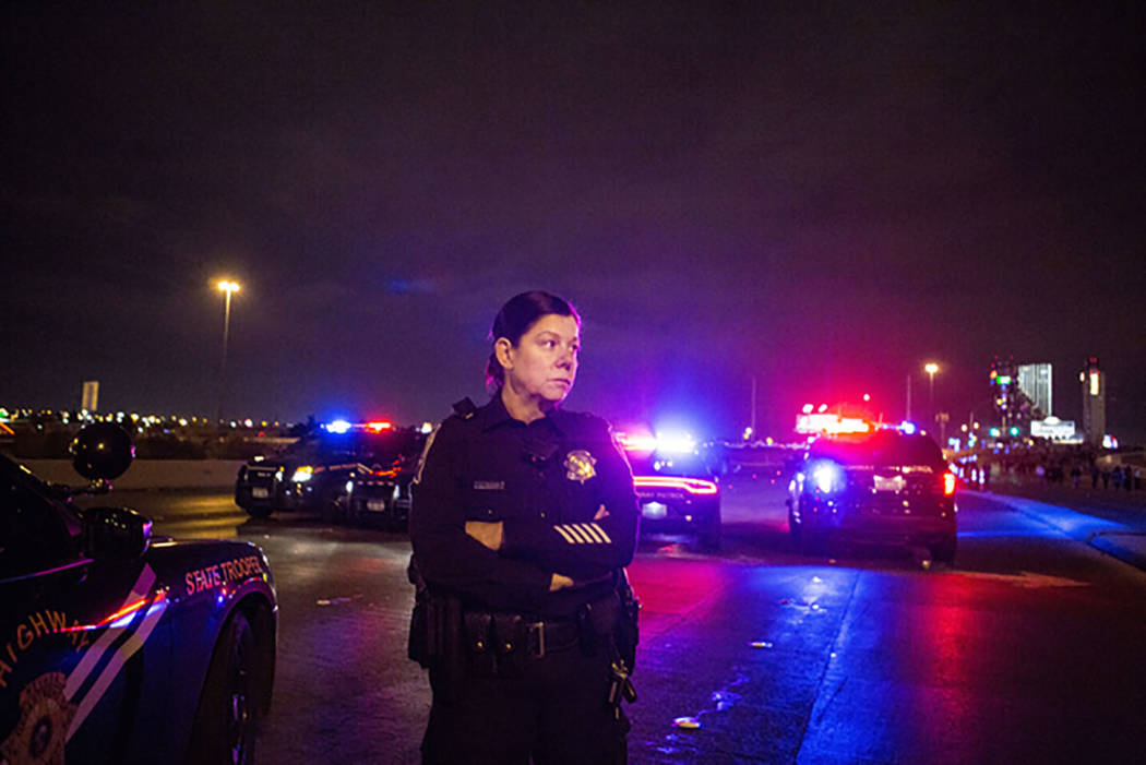 Nevada Highway Patrol trooper Angie Wolff patrols the Flamingo Road overpass while pedestrians walk toward the Las Vegas Strip on New Year's Eve, Dec. 31, 2016. (Elizabeth Brumley/Las Vegas Review ...
