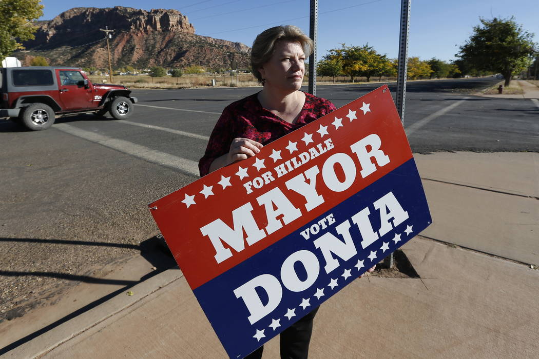 Donia Jessop holds her mayoral campaign sign outside her store in Colorado City, Ariz., last month.  (AP Photo/Rick Bowmer, File)