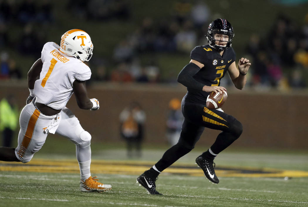 Missouri quarterback Drew Lock, right, scrambles away from Tennessee defensive lineman Jonathan Kongbo during the first half of an NCAA college football game Saturday, Nov. 11, 2017, in Columbia,  ...