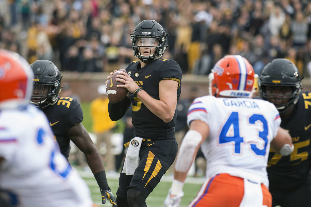 Missouri quarterback Drew Lock looks for an open receiver between Florida defenders during the first half of an NCAA college football game Saturday, Nov. 4, 2017, in Columbia, Mo. (AP Photo/L.G. P ...