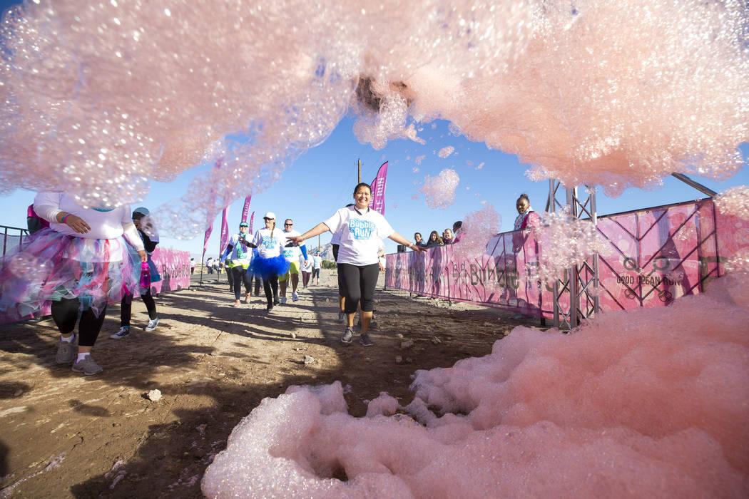 Participants run through foam sprayers during the Bubble Run 5K event at Sam Boyd Stadium in Las Vegas, Saturday, Nov. 18, 2017. Richard Brian Las Vegas Review-Journal @vegasphotograph