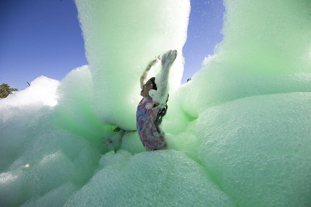 Ten-year-old Meleny Delgado runs under a green foam sprayer during the Bubble Run 5K event at Sam Boyd Stadium in Las Vegas, Saturday, Nov. 18, 2017. Richard Brian Las Vegas Review-Journal @vegasp ...