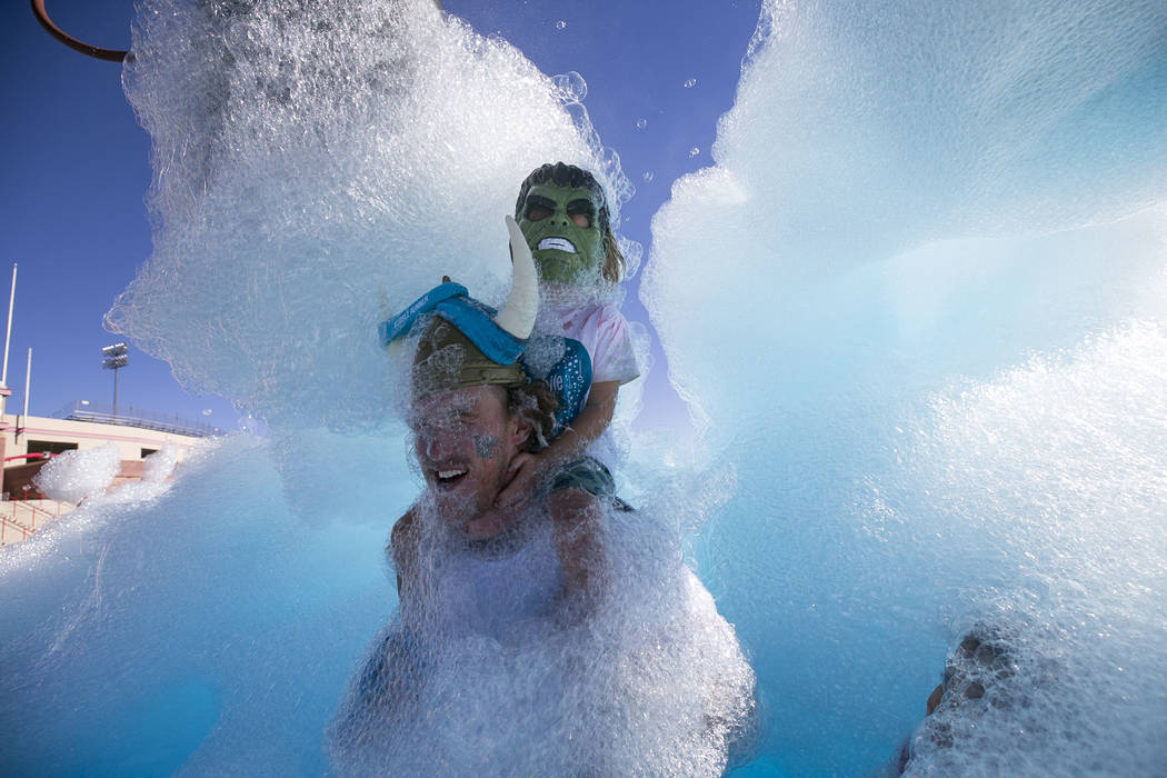 Tyler Fegert and his three-year-old son Hawkin run under a blue foam sprayer during the Bubble Run 5K event at Sam Boyd Stadium in Las Vegas, Saturday, Nov. 18, 2017. Richard Brian Las Vegas Revie ...
