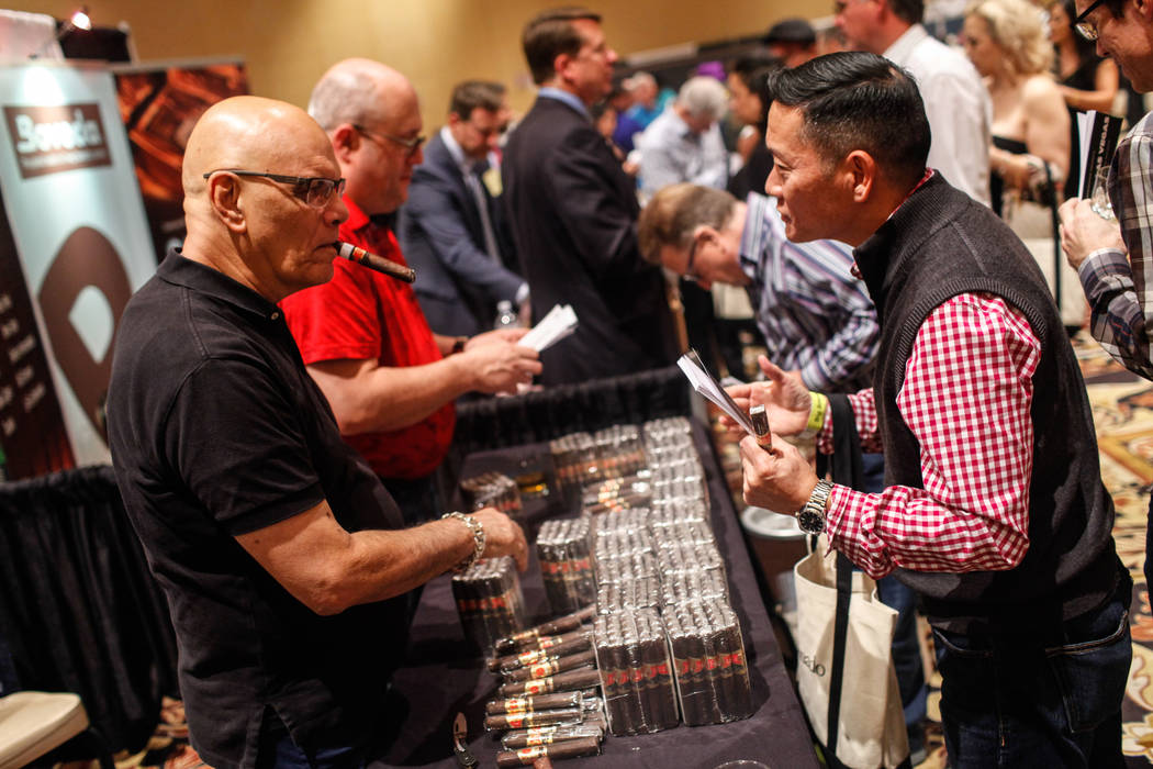 Ernesto Perez Carrillo, 66, owner of EP Carrillo, left, hands out cigars to patrons during the Cigar Aficionado's Big Smoke Las Vegas weekend event at The Mirage in Las Vegas, Saturday, Nov. 18, 2 ...