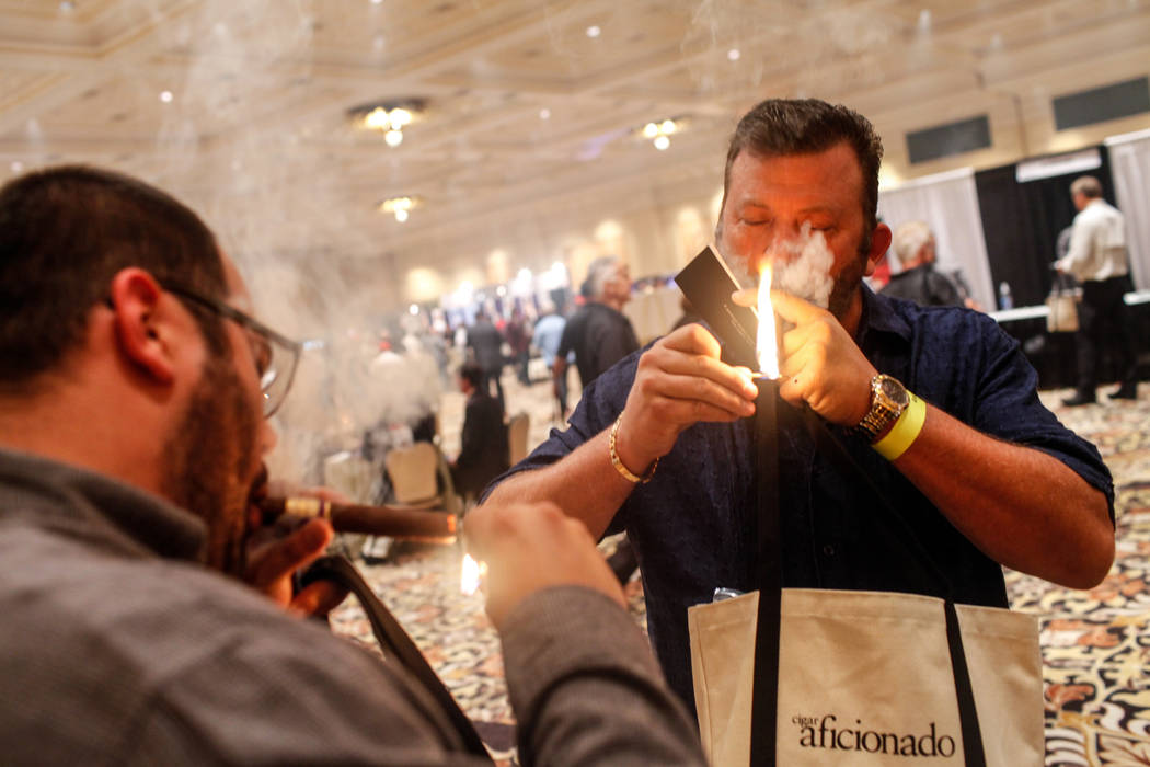 Nick Killion, 26, left, and his father Mike Killion, 48, right, both of Murrieta, Calif. light cigars during the Cigar Aficionado's Big Smoke Las Vegas weekend event at The Mirage in Las Vegas, Sa ...
