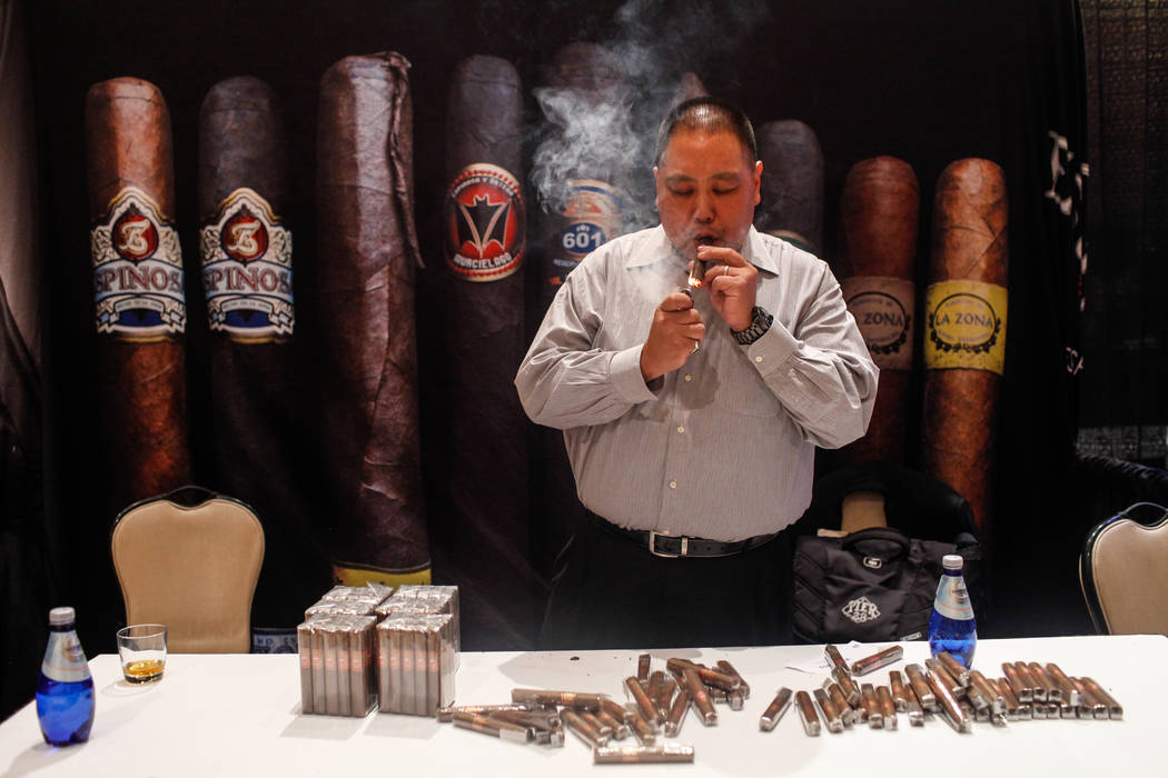 Tim Wong of Orange County, Calif., 45, lights a cigar at the Espinosa cigar table during the Cigar Aficionado's Big Smoke Las Vegas weekend event at The Mirage in Las Vegas, Saturday, Nov. 18, 201 ...