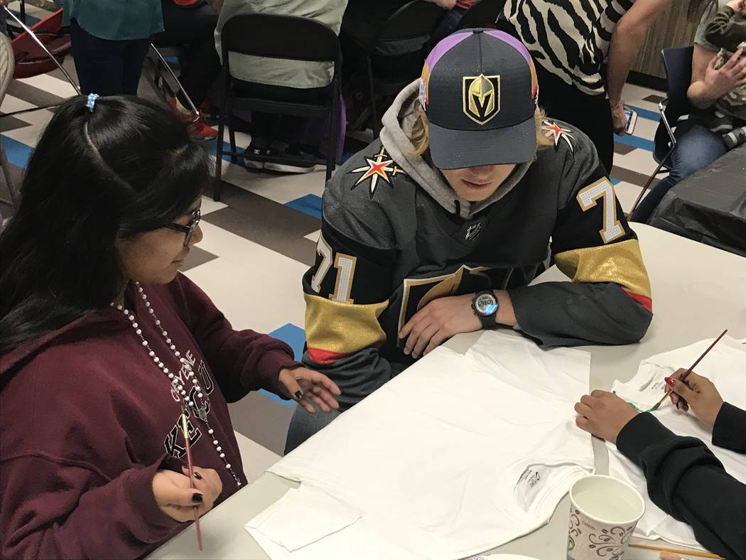 Golden Knights center William Karlsson, right, helps Fatima Vargas, 16, design a T-shirt Saturday at the Nevada Childhood Cancer Foundation. Karlsson was one of 11 Knights players who visited 50 p ...