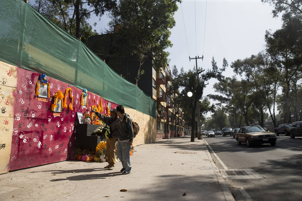 People walk next to a memorial for the victims who died after their apartment complex, Unidad Habitacional de Tlalpan, collapsed during the Sept. 19 earthquake in Mexico City, Mexico, Friday, Nov. ...