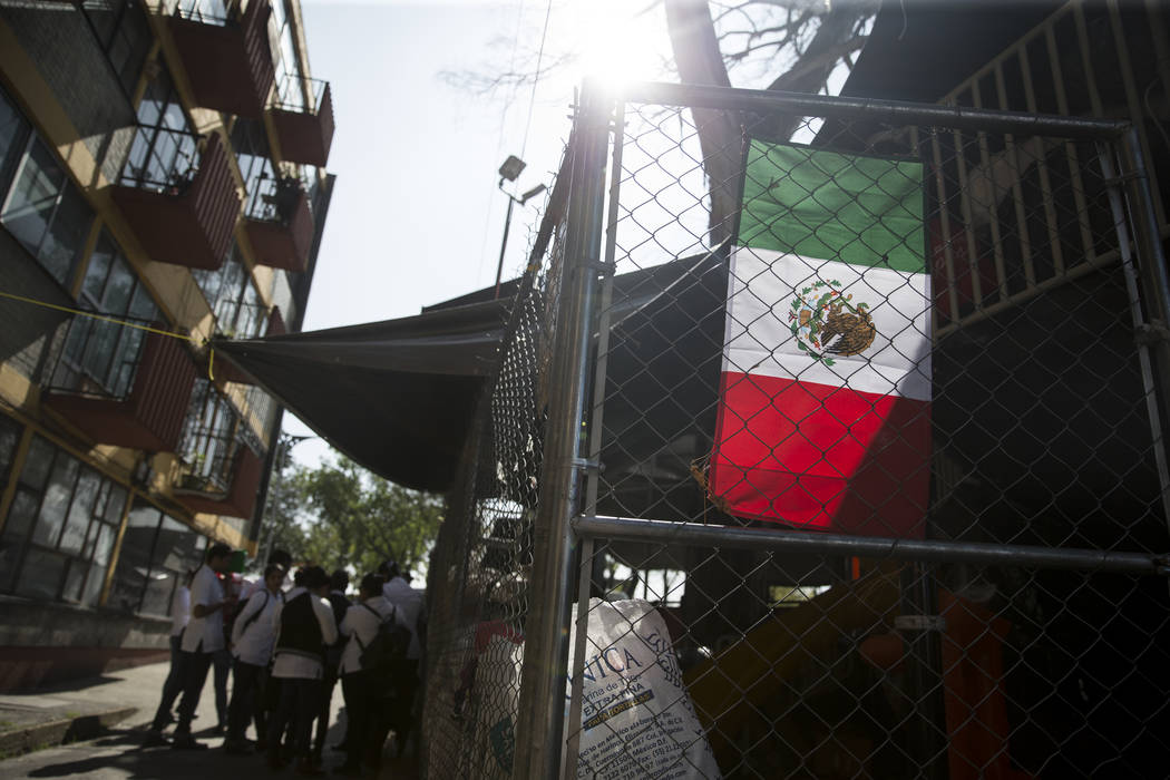 A Mexican flag hangs outside of an outdoor shelter created by victims living in the Unidad Habitacional de Tlalpan apartment complex, which suffered structural damage during the Sept. 19 earthquak ...