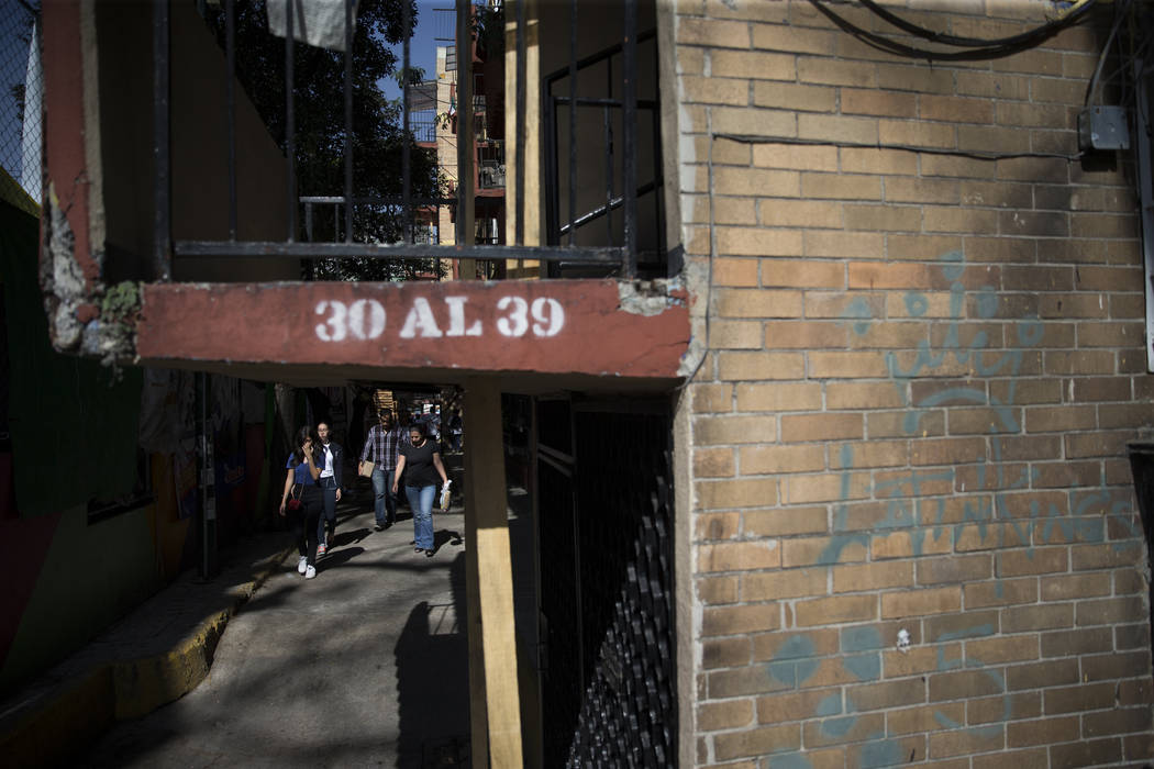 People walk by the uninhabited apartment complex, Unidad Habitacional de Tlalpan, which suffered structural damage during the Sept. 19 earthquake in Mexico City, Mexico, Friday, Nov. 17, 2017. An  ...