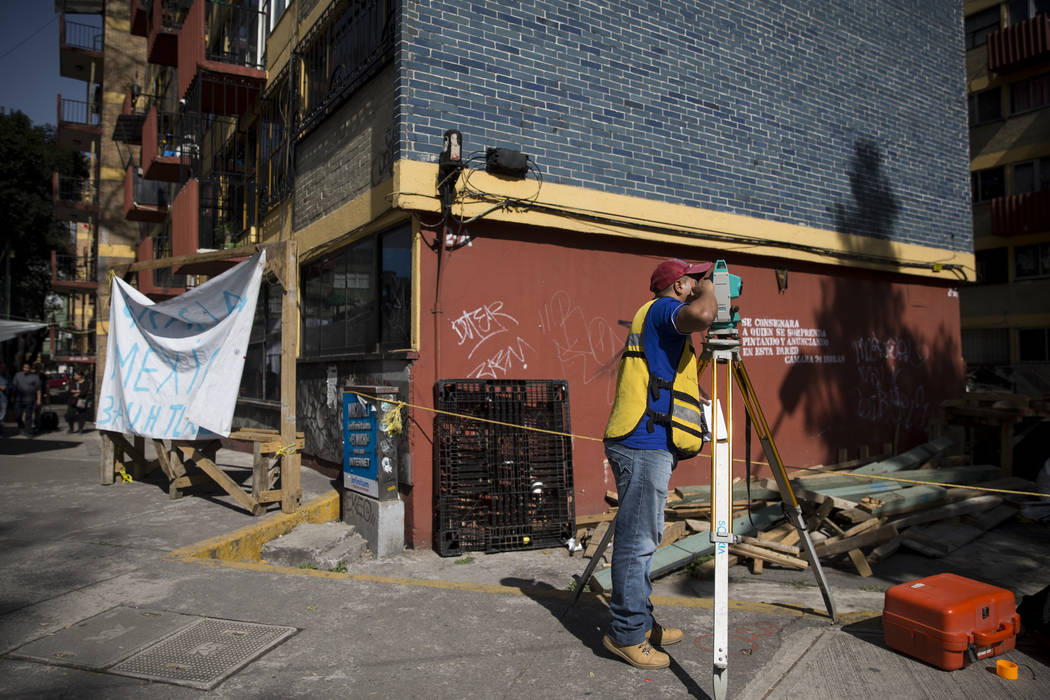 A worker outside of the uninhabited apartment complex, Unidad Habitacional de Tlalpan, which suffered structural damage during the Sept. 19 earthquake, takes measurements from the sidewalk in Mexi ...