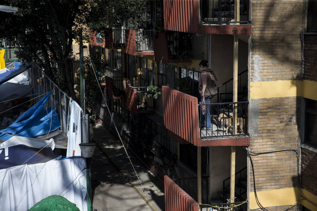 A woman walks up the stairs of the Unidad Habitacional de Tlalpan apartments complex, which was deemed unhabitable after suffering structural damage during the Sept. 19 earthquake in Mexico City,  ...