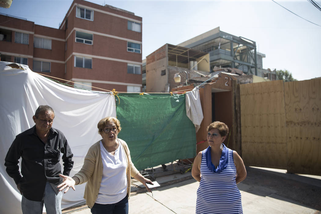 Gustavo Godinez Cadena, from left, his sister Georgina, and neighbor Elsa Garcia, outside of their homes and in front of Colegio Enrique Rebsamen elementary school, which collapsed during the Sept ...