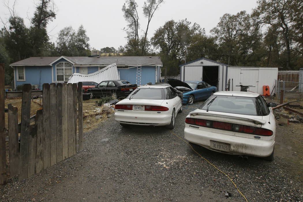 Cars are parked in front of the home of Kevin Janson Neal Wednesday, Nov. 15, 2017, in Rancho Tehama Reserve, Calif. (AP Photo/Rich Pedroncelli)