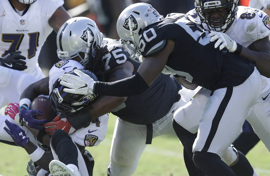 Oakland Raiders defensive tackle Darius Latham (75) and linebacker Nicholas Morrow (50) tackle Baltimore Ravens running back Alex Collins during an NFL football game in Oakland, Calif., Sunday, Oc ...