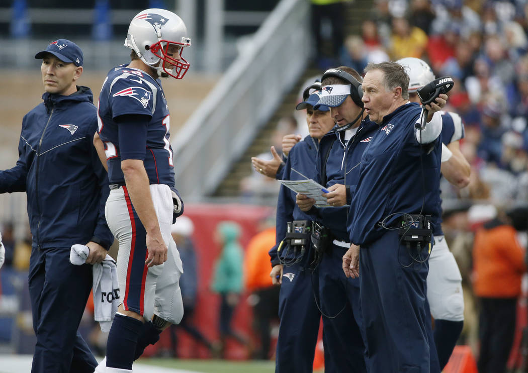 New England Patriots head coach Bill Belichick, right, instructs New England Patriots quarterback Tom Brady, left, during the second half of an NFL football game against the Los Angeles Chargers,  ...