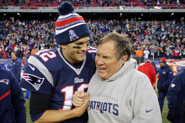 New England Patriots quarterback Tom Brady (12) celebrates with head coach Bill Belichick (R) after clinching the AFC East title with a 41-13 win over the Miami Dolphins at Gillette Stadium. Manda ...